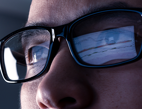 Close up image of a man in glasses looking at a computer.
