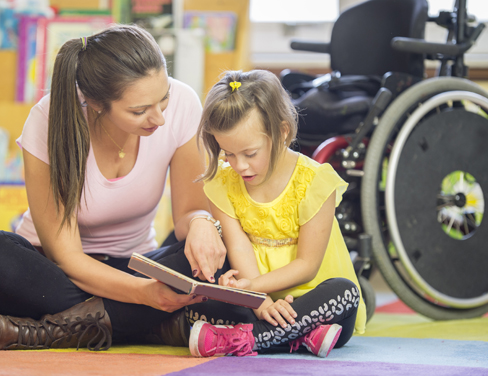 Caregiver reading a book with a child