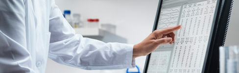 person wearing a lab coat pointing at data on computer screen