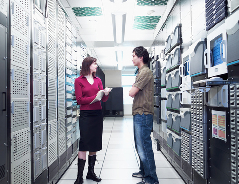 Man and woman standing in computer server room.