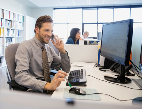 Businessman talking on cell phone at office desk.
