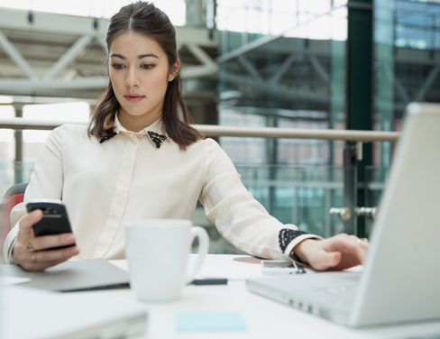 Businesswoman using laptop and texting with cell phone in conference room.