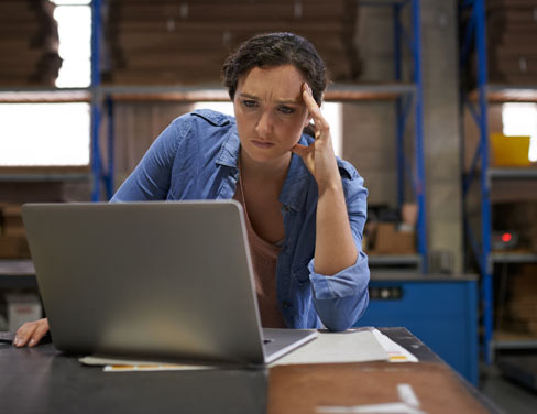 woman in a warehouse looking frustrated at laptop
