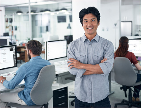 Professional man standing in office, smiling because of his new enterprise content management system