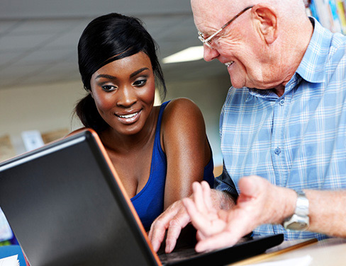 Elderly teacher with a student looking at a laptop