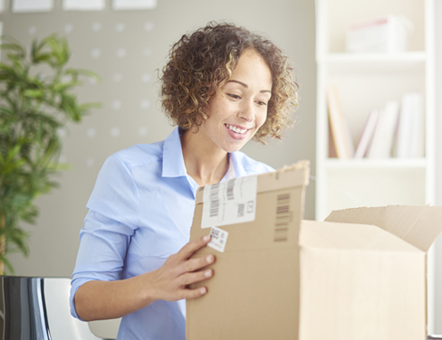 Young woman in her home office holds mail package.