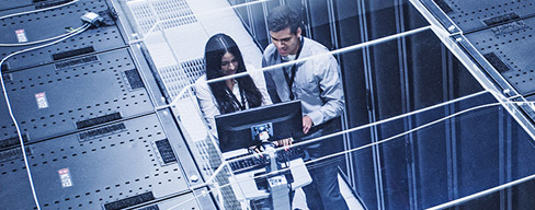 Photo of two people in a server room.