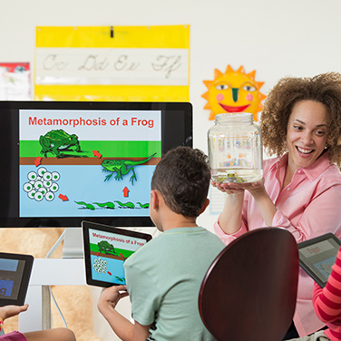 kids in classroom looking at large screen with tablets displaying infomation from large screen