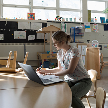Teacher grading papers at laptop in classroom