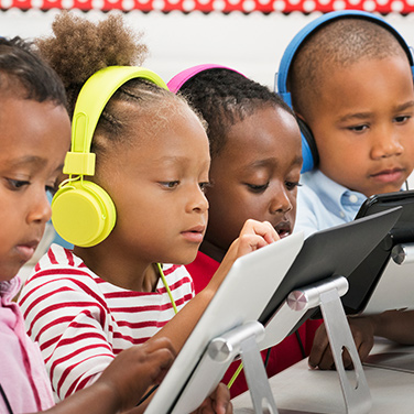 young children using tablets wearing headphones