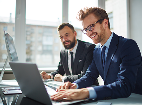 Photo of businessmen men smiling at a computer