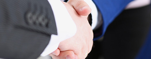 Closeup photo of two people in suits shaking hands.
