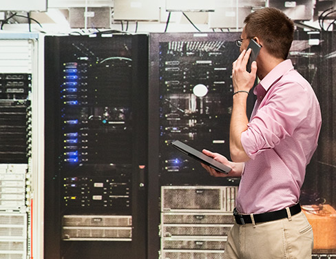 Photo of a man talking on his phone in front of a server.