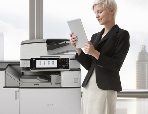 Woman standing next to printer looking at a printed document.