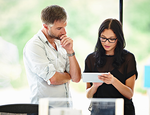 Photo of a woman talking to a man holding a tablet
