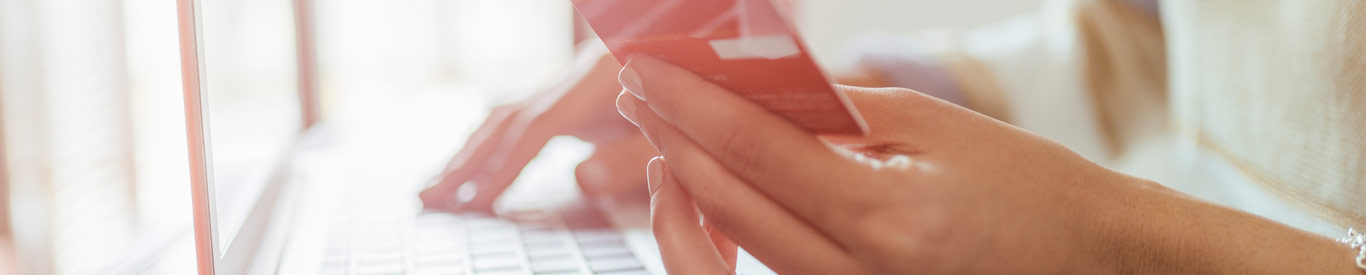 close up of hands typing on keyboard and holding credit card making online purchases