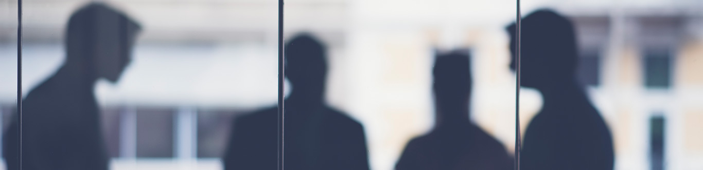 Photo of people blurred behind a wall of glass.