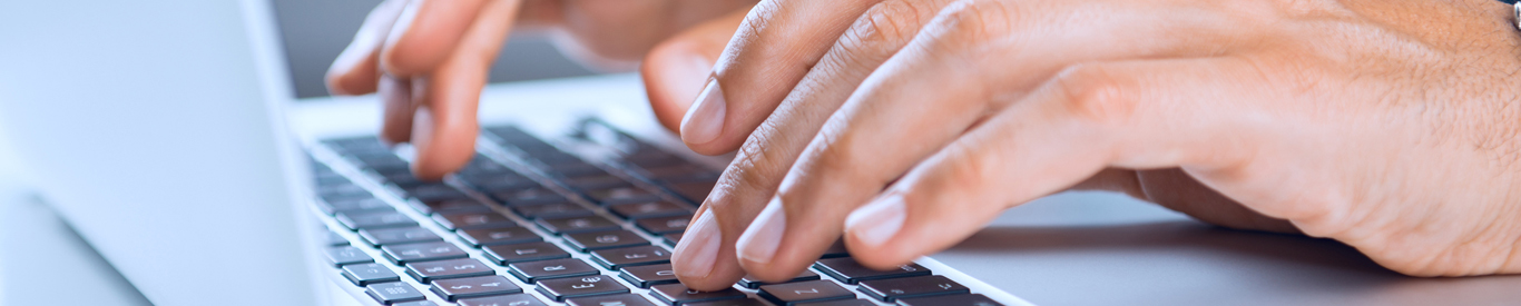 Close up image of someone using a laptop computer.