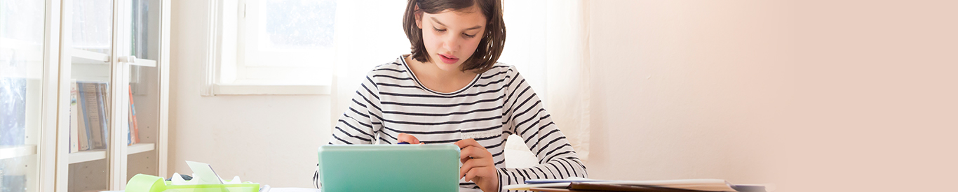 young girl doing homework on tablet