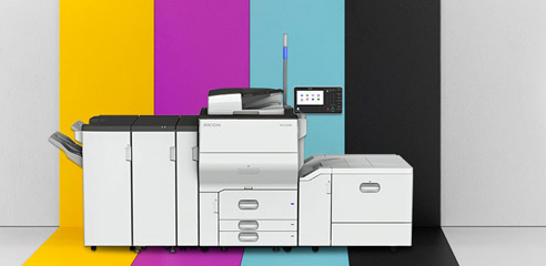 Photo of a Pro C5200s/C5210s printer in front of a colored background.